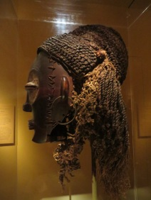 Ewo (woman) has tattoos, earrings, and elaborate hair